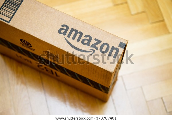 PARIS, FRANCE - JAN 28, 2016: Amazon logotype printed on cardboard box side seen from above on a wooden parwuet floor. Amazon is an American electronic e-commerce company distribution worlwide