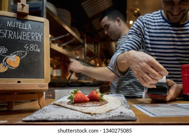 Paris, France, Jan 28 2019 :  Storekeeper selling French strawberry crepe using a card machine