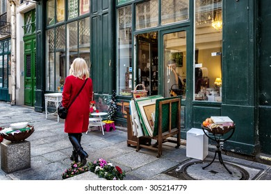 PARIS, FRANCE - JAN 3, 2014: Antique shop on a side street in the historic neighborhood of Le Marais. Items for sale on the sidewalk. An unidentified woman in a red coat walks by.