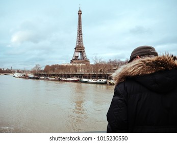 PARIS, FRANCE - JAN 30, 2018: Parisian senior man watch the swollen river Seine near the Eiffel Tower as the river's embankments overflow after days of heavy rain