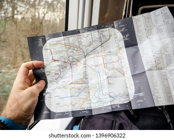 Paris, France - Jan 30, 2018: Hand holding POV map of Parisian New Paris Metro Map with station names and connections commuting from Charle de Gaulle airport to city center