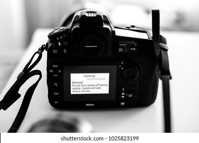PARIS, FRANCE - JAN 31, 2018: Black and white Nikon DSLR Camera Professional updating firmware with message on the screen: Do not turn camera off during update