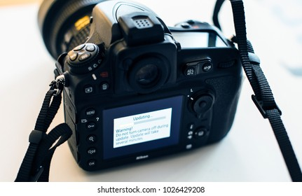 PARIS, FRANCE - JAN 31, 2018: Display of Nikon DSLR Camera Professional updating firmware with message on the screen: Do not turn camera off during update