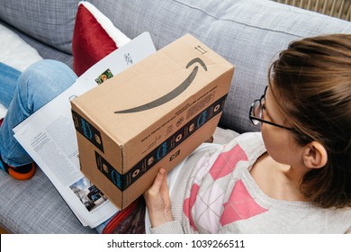 PARIS, FRANCE - JAN 6, 2018: Woman on the couch reading newspaper and preparing to unbox the Amazon Prime parcel