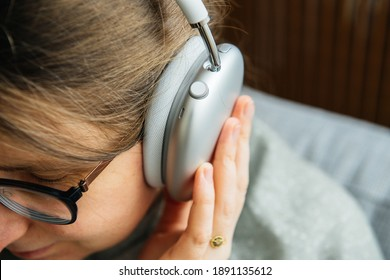 Paris, France - Jan 7, 2020: musicophile woman listens to new Apple Computers AirPods Max over-ear headphones with Adaptive EQ, Active Noise Cancellation, Transparency mode h1 chips and Siri