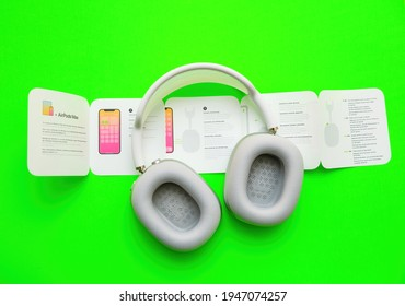 Paris, France - Jan 7, 2021: View from above of unboxing process of new AirPods Max wireless Bluetooth over-ear headphones created by Apple Computers - instruction manuals on vivid acid green