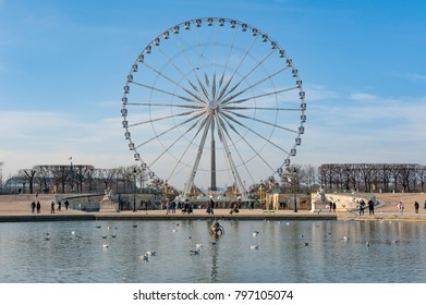 Paris, France - Jan 8, 2018 :  Ferris wheel against blue sky from the Tuileries park with a pond in the foreground