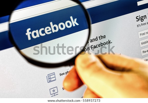 Paris, France - January 03, 2017 : Photo of Facebook homepage on a monitor screen through a magnifying glass.