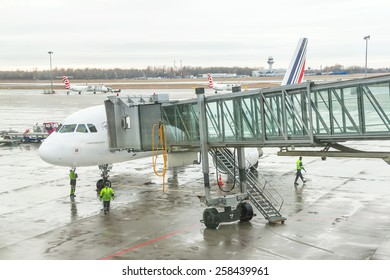 Paris, France - January 13, 2015: Airport workers (crew) are preparing for disembarking  passengers near terminal gate. Disembarking of airplane. World' s travel, air transport concept.
