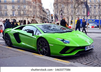 Paris, France - January 13th 2019 : Profil of a green Lamborghini aventador parked on the Champs-Elysees, with people.