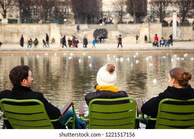 PARIS, FRANCE - JANUARY 14, 2018: Tourists and Parisians relaxing near pond at Tuileries Garden. Friends talk.