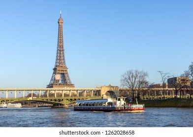 Paris, France - January 14, 2018: Sunset over Bir-hakeim bridge with boat in foreground and Eiffel Tower in background - Paris, France