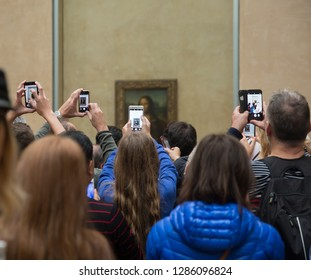 PARIS, FRANCE - January 15, 2019: Visitors take photos of Leonardo DaVinci painting Mona Lisa at the Louvre Museum. The painting is one of the world's most famous.