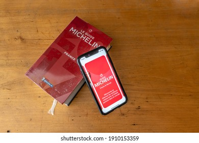Paris, France - January 15, 2020 - Red Michelin guide book and smartphone application, which reviews restaurants.