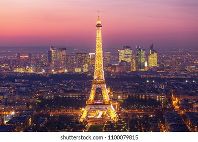 PARIS, FRANCE. JANUARY 16, 2012 : Eiffel Tower at Night with Paris Skyline and modern buildings of La Défense district in the background