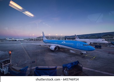 PARIS, FRANCE - JANUARY 18, 2017: Planes of KLM and Airfrance on a terminal of Charles de Gaulle Airport at dusk. It's also known as Roissy Airport is the largest international airport in France.