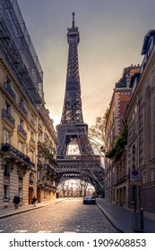 Paris, France - January 20, 2021: A back alley in Paris showcasing the architecture of the buildings with the Eiffel Tower in the background