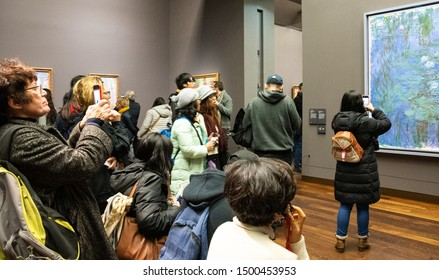 PARIS, FRANCE - JANUARY 6, 2019: Visitors admire and take photos of Blue Water Lilies by Claude Monet in Musee d'Orsay famous for its impressionist and post-impressionist collections