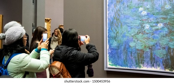 PARIS, FRANCE - JANUARY 6, 2019: Visitors admire and take photos of Blue Water Lilies by Claude Monet in Musee d'Orsay famous for its large impressionist and post-impressionist collections
