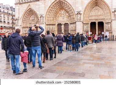 Paris, France - January 9, 2015:  Long queue (crowd) of people waiting in line to Notre Dame de Paris. People queueing in front of entrance.  Notre Dame is one of the most popular destinations.