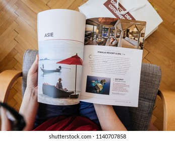 PARIS, FRANCE - JUL 1, 2018: French woman reading on wooden office table travel catalogue with luxury destination - view from above destination Asia