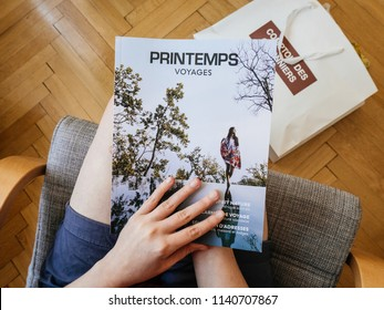 PARIS, FRANCE - JUL 1, 2018: French woman reading on wooden office table travel catalogue with luxury destination offered by Printemps fashion shopping gallery - view from above cover magazine