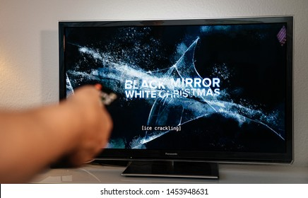 Paris, France - Jul 10, 2019: Senior man hand turning with remote control watching the Black Mirror on Netflix - it is a British science fiction anthology television series created by Charlie Brooker,
