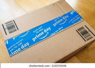 PARIS, FRANCE - JUL 12, 2108: Amazon Prime Day cardboard parcel on wooden parquet floor with special blue scotch tape for the Prime Day offering a day of deals, discounts, and unabashed shopping