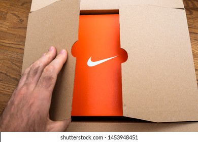 Paris France - Jul 13 2019: Above view unboxing open sport running shoes equipment manufactured byu Nike sportswear - cardboard box open with white logotype