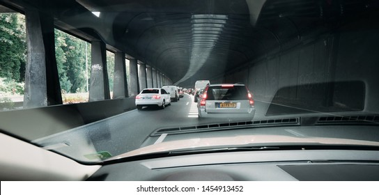 Paris, France - Jul 15, 2018: Wide image POV personal perspective and the front driving Volvo V70 car in traffic jam exiting the tunnel of Boulevard peripherique in Paris, France