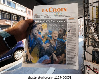 PARIS, FRANCE - JUL 16, 2018: Man buying La Croix newspaper announcing France champion title after French national football team won their FIFA World Cup 2018 final game against Croatia in Moscow