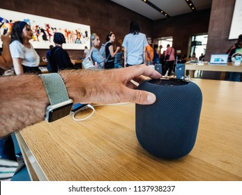 PARIS, FRANCE - JUL 16, 2018: Man touching Siri new Apple Store the latest Apple Computers HomePod smart speaker with Siri and Apple Music