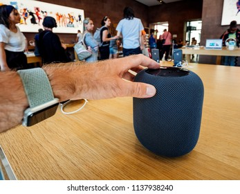 PARIS, FRANCE - JUL 16, 2018: Man admiring new Apple Store the latest Apple Computers HomePod smart speaker with Siri and Apple Music