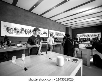 PARIS, FRANCE - JUL 16, 2018: Modern Apple Mac store main hall with handsome man admiring playing with latest iPhone X smartphone next to HomePod speaker - black and white