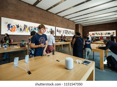 PARIS, FRANCE - JUL 16, 2018: Interior of Apple Mac store main hall with handsome man admiring playing with latest iPhone X smartphone next to HomePod speaker