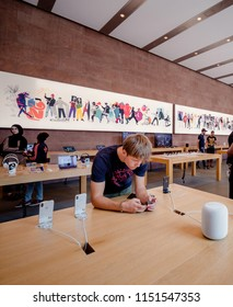 PARIS, FRANCE - JUL 16, 2018: Modern Apple Mac store main hall with handsome man admiring playing with latest iPhone X smartphone next to HomePod speaker