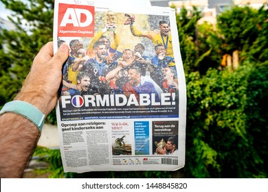 PARIS, FRANCE - JUL 16, 2018: Man holding Dutch newspaper announcing France champion title after French national football team won their FIFA World Cup 2018 with Breaking Formidable title