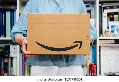 PARIS, FRANCE - JUL 4, 2018: Woman receiving Amazon Prime package delivered preparing to do the unboxing, proud Amazon Prime client with library in background