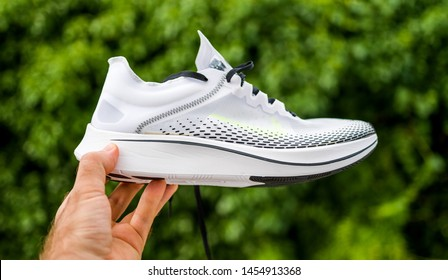 Paris, France - Jul 8, 2019: Athlete man hand holding presenting new running shoes Nike Zoom Fly SP Fast against green background