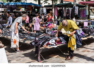 Paris, France - Jule 09, 2017: Men choose clothes at the flea Aligre Market (Marche d'Aligre) in the Bastille district.