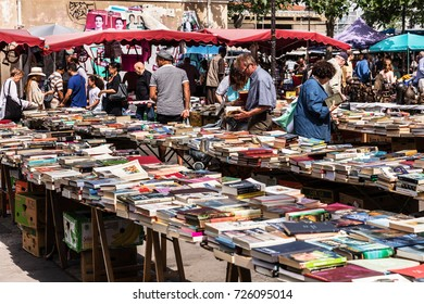 Paris, France - Jule 09, 2017: People choosing rare and used books at the historic flea Aligre Market (Marche d'Aligre) in the Bastille district.
