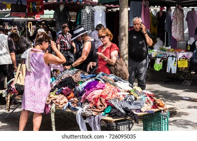 Paris, France - Jule 09, 2017: Senior women choosing clothes at the flea Aligre Market (Marche d'Aligre) in the Bastille district.