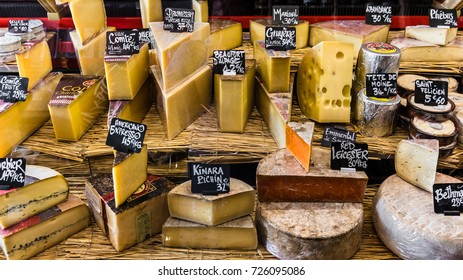 Paris, France - Jule 09, 2017:  A large selection of different french and italian cheeses on the counter of a small store at the Aligre Market (Marche d'Aligre) in the Bastille district.