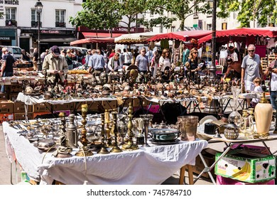 Paris, France - Jule 09, 2017: People choosing rare and used books, wooden masks and figures of African culture at the historic flea Aligre Market (Marche d'Aligre) in the Bastille district.