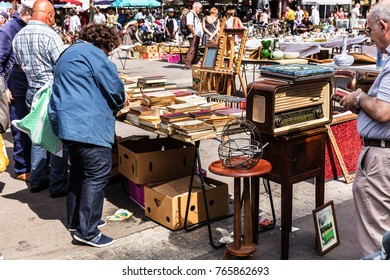 Paris, France - Jule 09, 2017: People choosing rare and used books, vintage goods at the historic flea Aligre Market (Marche d'Aligre) in the Bastille district.