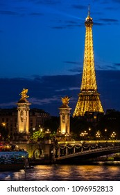 Paris, France - July 01, 2017: Beautiful night illumination of Eiffel Tower and Pont Alexandre III Bridge over river Seine decorated with ornate art nouveau lamps and sculptures.