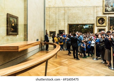 "Paris, France - July 01, 2017: Visitors take photo of Leonardo DaVinci's ""Mona Lisa"" at the Louvre Museum. The painting is one of the world's most famous."