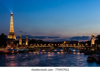 Paris, France - July 02, 2017: Beautiful night illumination of Eiffel Tower and Pont Alexandre III Bridge over river Seine decorated with ornate art nouveau lamps and sculptures in the summer.