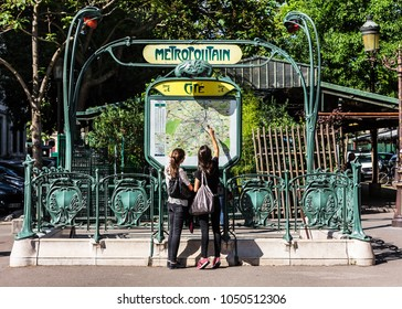 Paris, France - July 03, 2017:  Young tourists in Paris, using map and looking for the direction at the entrance to the Paris Metropolitain (subway) at the Cite metro station.