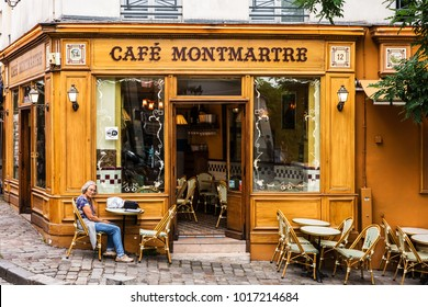 Paris, France - July 06, 2017: The charming Cafe Montmartre on Montmartre hill. Woman sitting at the table. Montmartre with traditional french cafes is one of the most visited landmarks in Paris.